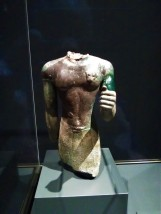 Torso of a Priest Wearing a Leopard Skin; Egyptian, Dynasties 25-26, 700-600 BCE; found in the Temple of Hera on Samos. As early as the mid-seventh century BCE, Greeks returning to their homes from Egypt brought back objects to be dedicated in sanctuaries. Some votives found in Greece, however, may have been donated by Egyptians. The pharaoh Amasis II (ruled 570-527 BCE) himself was renowned for giving valuable works to temples on the Greek islands of Samos and Rhodes. This torso was one of many Egyptian bronze offerings deposited on Samos.