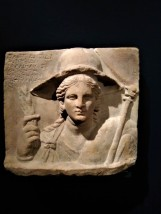 Relief with Isis. Greek, 250-150 BCE; found in Dion, Macedonia, Greece. The goddess Isis began to be worshipped outside Egypt during the Ptolemaic period (323-30 BCE). In this relief from Macedonia, she is depicted as a fertility deity equated with the Greek goddess Demeter. She holds a sheaf of wheat and a scepter decorated with a solar disk. Her broad-rimmed hat may have had a crescent moon attached, and her drapery is tied at the shoulder with a characteristic knot. The inscription names a Greek couple, Kallimachos and Kleta, who dedicated this votive offering to the Egyptian deities Serapis, Isis, and Anubis.