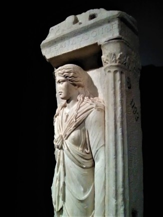 """Gravestone of Alexandra, Priestess of Isis. Roman, made in Athens, 125-150 CE; found in the Kerameikos Cemetery, Athens. An Athenian priestess of Isis is shown in the guise of the goddess. The Greek inscription identifies her as """"Alexandra, of the deme of Oe, wife of Ktetos."""" Her curled tresses, long-sleeved tunic, and fringed mantle crossed over the chest resemble Isis's hairstyle and attire. She carries objects associated with the deity's cult - a situla (ritual vessel) and a sistrum (rattle, now missing)."""