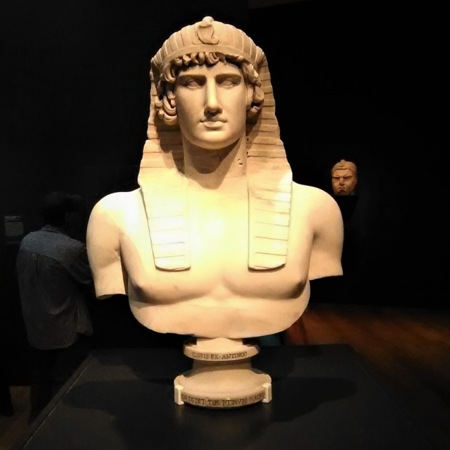 Bust of Antinous. Roman, 131-138 CE; found in Hadrian's Villa, Tivoli, Italy. Antinous, the young companion of the emperor Hadrian (ruled 117-138 CE), drowned in the Nile in 130 CE and was posthumously honored with a cult that was celebrated throughout the Roman Empire. Hadrian's Villa at Tivoli displayed numerous portraits of Antinous in the guise of a pharaoh or the underworld god Osiris, wearing a traditional nemes headdress with a uraeus (royal cobra).