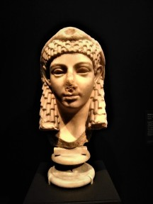 Head of Isis. Roman, 40 BCE-100 CE, found in Rome. Carved in fine Greek marble, Isis is shown wearing a traditional Egyptian three-part, curled wig as well as a headdress in the form of a dove (the bird's head is now missing). The dove indicates that Isis was assimilated with the Greek goddess Aphrodite. The complete statue may have stood in a temple of Isis and Serapis on the Via Labicana in Rome.