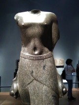 Torso of Harchebi (Archibios); Ptolemaic, 170-116 BCE. Harchebi was an Egyptian priest who served as dioiketes (finance minister) during the reign of Ptolemy VIII (170-116 BCE). He wears a traditional three-part kilt and holds both arms tightly at his sides, clenching rolls of cloth, a sign of status. The relief scene at the top of the inscribed back pillar shows him making offerings to the gods of Mendes, in the eastern Nile Delta: Harpokrates, the Ram of Mendes, and Hatmehyt. The hieroglyphic inscription on his belt provides his Egyptian name as well as its Greek form, Archibios. As a high official in the Ptolemaic administration, he used both names in performing his duties within a bilingual society.