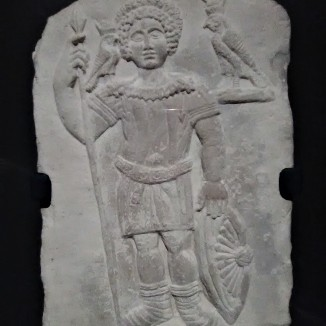 Gravestone of a Soldier. Romano-Egyptian, c. 300 CE. The deceased is shown in military garb, holding a spear and shield, with a wreath in his curly hair. Two falcons, each wearing the Double Crown of Upper and Lower Egypt, represent his devotion to the god Horus. The unnamed man was likely an Egyptian who served in the Roman army.