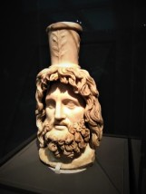 Head of Serapis. Roman, c. 200 CE; found in Walbrook, City of London. Worship of the god Serapis, the consort of Isis, spread from Egypt to the far reaches of the Roman Empire. This marble head was discovered in the Temple of Mithras in London in 1954. It may have been dedicated there when the Roman emperor Septimius Severus (ruled 193-211 CE) visited the city in 208 CE. The North African-born ruler particularly revered Serapis and styled his own portraiture on the deity's appearance.